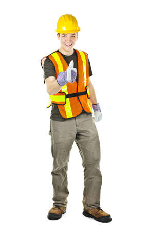 Smiling male construction worker showing thumbs up in safety vest and hard hat photo