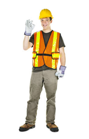 Smiling male construction worker showing okay sign standing isolated on white background photo
