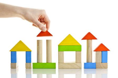 Hand bouwen van huizen van houten blok speelgoed geïsoleerd op witte achtergrond