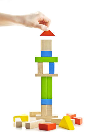 Hand building tower of wooden blocks isolated on white background photo