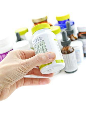 Botella de medicina para leer la etiqueta de mano Foto de archivo