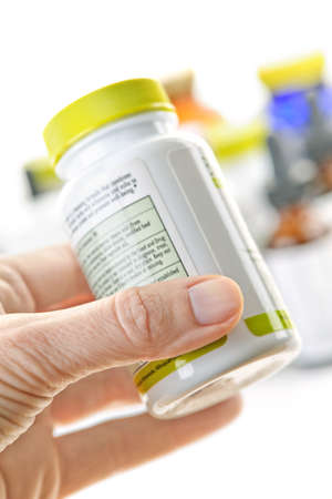 and vitamin: Hand holding medicine bottle to read label Stock Photo