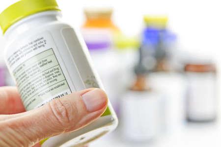 Hand met geneeskunde fles etiket te lezen