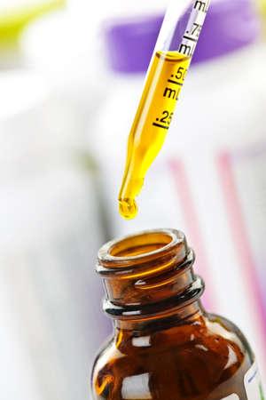 doses: Close-up van vloeibare geneeskunde in glas de druppelaar en fles