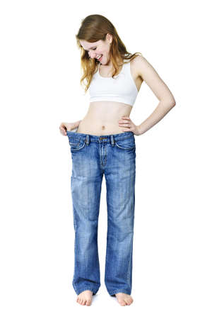 Smiling fit young woman in loose old jeans after losing weight isolated on white