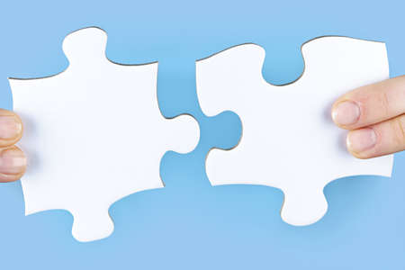 close fitting: Fingers joining large white blank jigsaw puzzle pieces