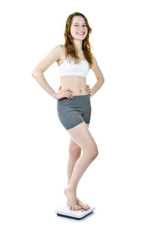 Smiling fit young woman standing on bathroom scale isolated on white Archivio Fotografico
