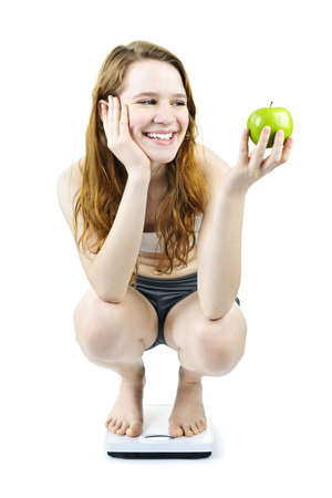 Healthy happy young woman holding apple on bathroom scale isolated on white Stock Photo - 9434389