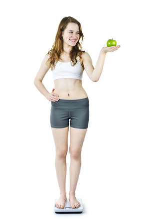 Healthy happy young woman holding green apple standing on bathroom scale photo