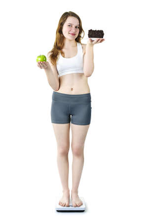 Tempted young woman holding apple and chocolate cake standing on scale Stock Photo - 9434448