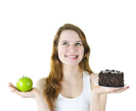 indulgere: Tentati young woman holding apple e fare una scelta di torta al cioccolato