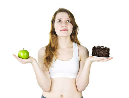 indulging: Tempted young woman holding apple and chocolate cake making a choice