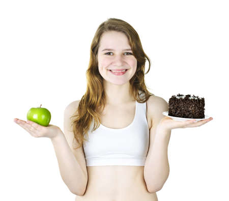 Smiling young woman holding apple and chocolate cake photo