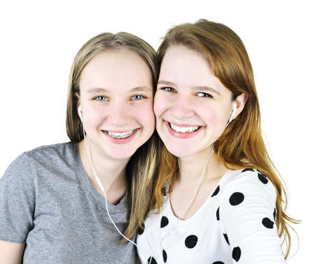 earphone: Portrait of two teenage girl friends listening to music sharing earphones