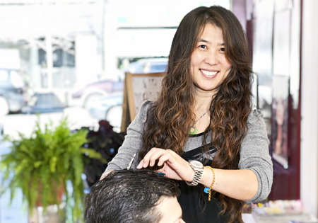 Happy hairdresser cutting hair in her salon photo
