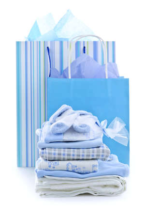 Gift bags and infant clothes for baby shower isolated on white photo