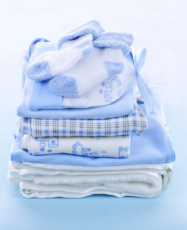 Stack of boy infant clothing for baby shower on blue background photo