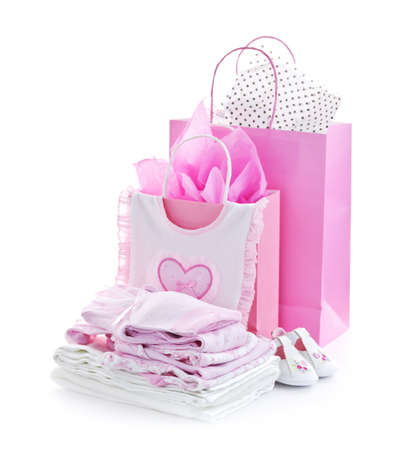 Pink gift bags and infant clothes for girl baby shower isolated on white photo