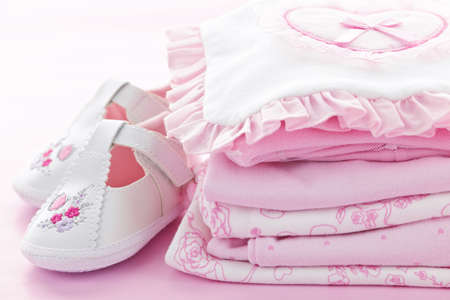 pile of clothes: Pink infant girl clothing and shoes for baby shower