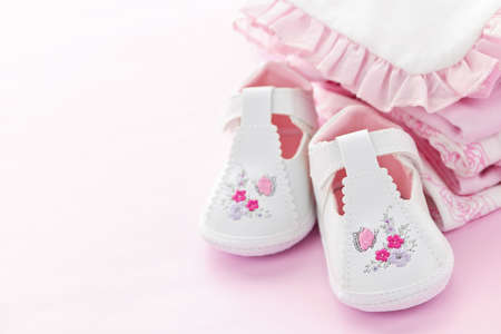 Infant girl clothing and shoes for baby shower on pink background Stock Photo - 9660663