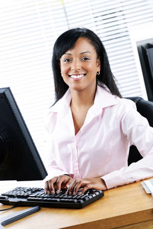 of office: Young smiling black business woman at desk typing on computer