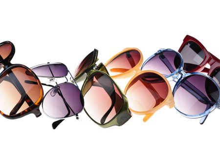 Different styles of tinted sunglasses on white background photo