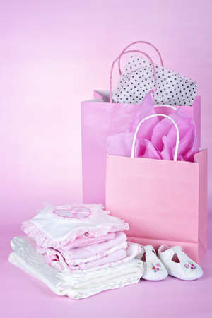 Gift bags and infant clothes for girl baby shower on pink background Stock Photo - 9734584