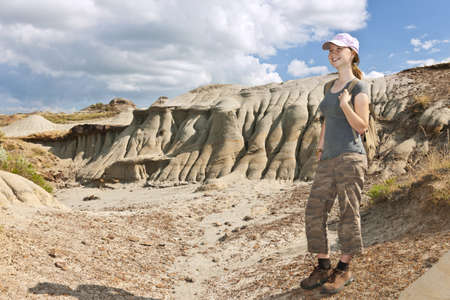 provincial: Smiling young girl standing at the Badlands in Dinosaur provincial park, Alberta, Canada Stock Photo