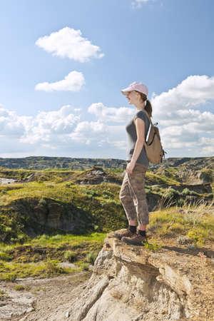 Happy female hiker looking onto the Badlands in Dinosaur provincial park, Alberta, Canada photo