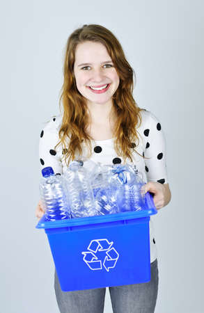 carrying: Smiling young woman carrying full recycling box on blue background