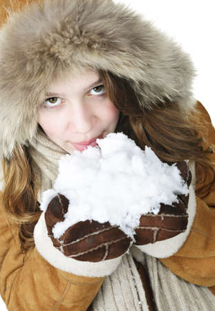 Playful young woman in winter coat with fur hood holding and tasting snow photo