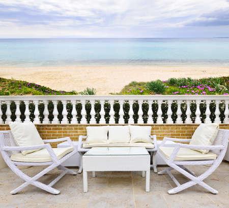 patio furniture: Patio con mobili in vimini bianco con vista della spiaggia mediterranea in Grecia