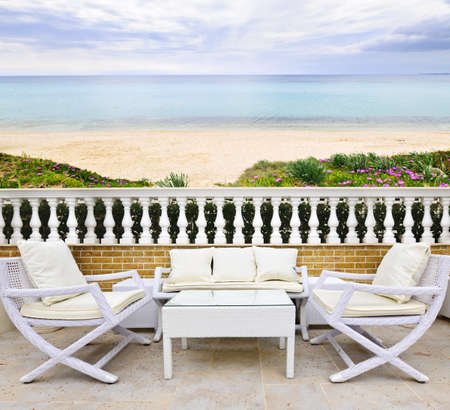 Patio with white wicker furniture with view of Mediterranean beach in Greece photo