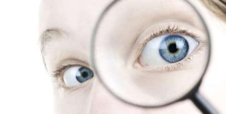 globo ocular: Ojo azul femenina a trav�s de la lupa de cerca Foto de archivo