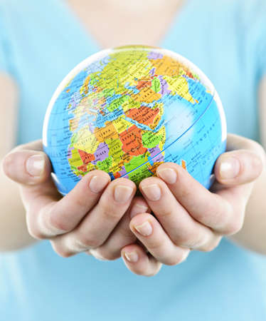 holding close: Globe of the planet Earth held in young female hands