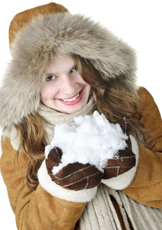 Playful young woman in winter coat with fur hood holding pile of fresh snow photo