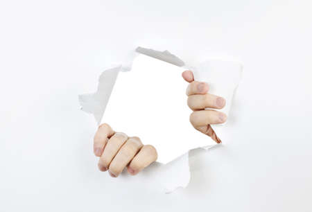 Hands ripping a hole in white paper with torn edges