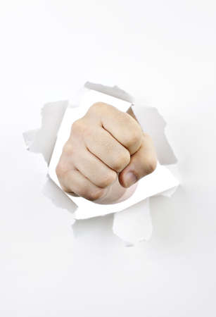 Fist punching through hole in white paper photo