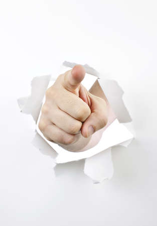 Finger pointing through hole torn in white paper photo
