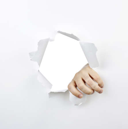 Hand ripping a hole with torn edges in white paper