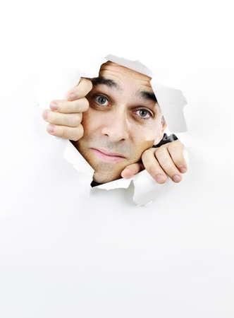 clawing: Uomo curioso guardando attraverso il buco strappato nel libro bianco