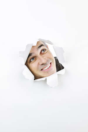 see through: Curious man looking up through hole ripped in white paper