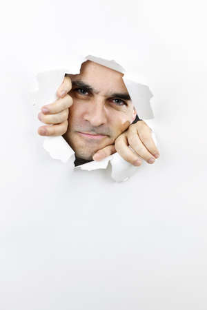 Hole in paper with angry man looking through photo
