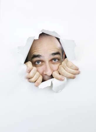 hombre asustado: Agujero en papel con miedo hombre mirando a trav�s de