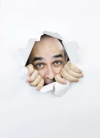 Hole in paper with scared man looking through Stock Photo - 9865754