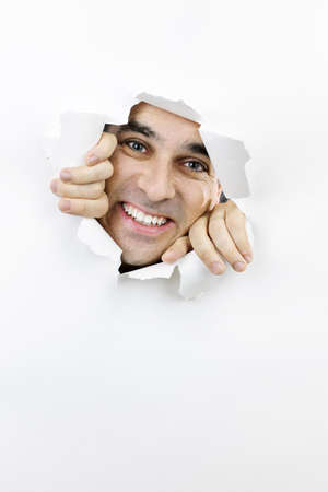 Hole torn in paper with smiling man looking through