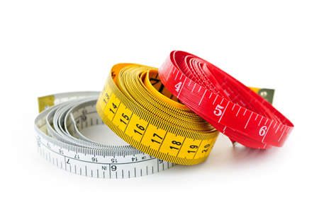 cintas metricas: Tres cintas coloridas de medici�n enrolladas sobre fondo blanco Foto de archivo