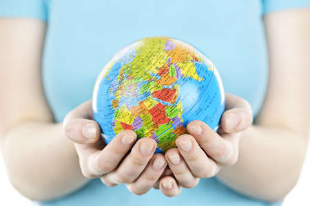 hand holding globe: Globe of the planet Earth held in young female hands