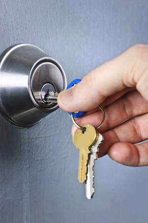 Hand inserting keys in door lock close up