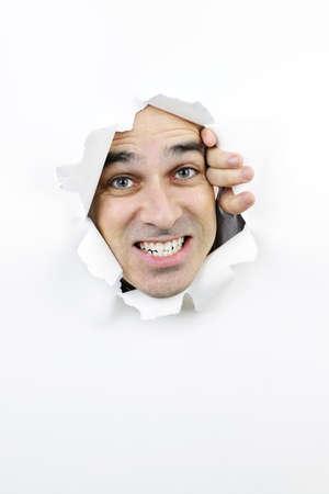 clawing: Hole in carta con uomo arrabbiato guardando attraverso Archivio Fotografico